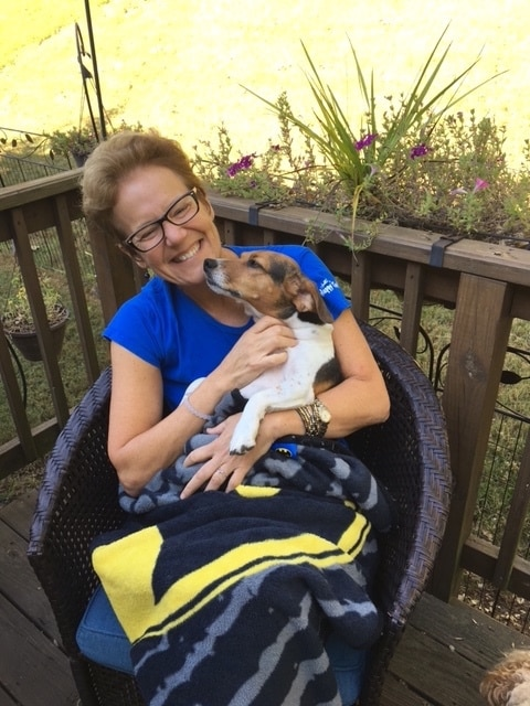 Woman in blue shirt sitting outside smiles as she holds her beagle.