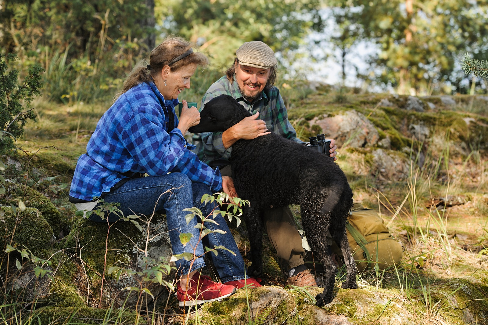 Senior couple playing with their pet dog while out hiking. The dog is a curly haired retriever.